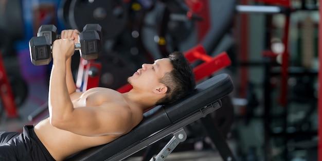 Спортивный человек, тренировка с гантелями в тренажерном зале