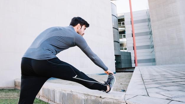 Спортивный человек, согревающий на улице