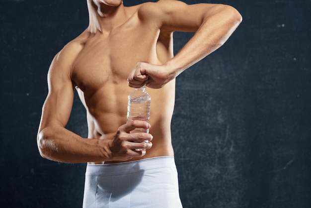 Sporty man in white shorts pumped up body water bottle healthy fitness