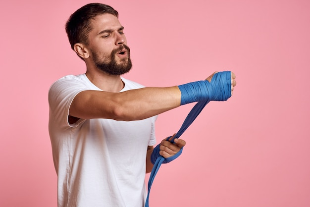 Sporty man in a white t-shirt boxing bandages on the hands of a workout lifestyle pink space.