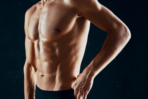 タオルの暗い背景でポンプアップされた筋肉の体を持つスポーティな男 Premium写真
