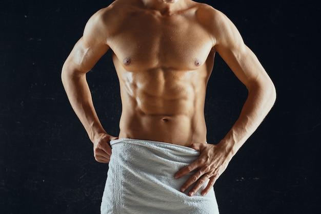 수건 어두운 배경에 펌핑된 근육질의 몸을 가진 스포티 한 남자