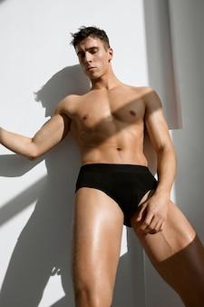 暗いショーツスタジオ明るい背景でポンプアップされた筋肉の体を持つスポーティな男