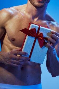 彼の手の休日に贈り物を持ったポンプで胴体を持ったスポーティな男
