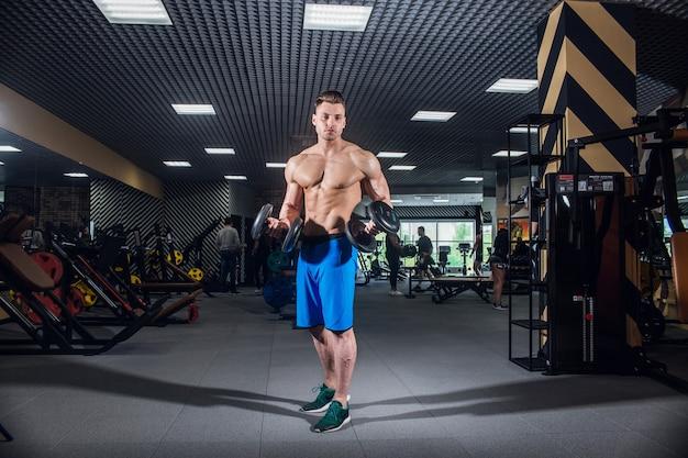 큰 근육과 넓은 등을 가진 스포티한 남자는 체육관, 피트니스 및 펌핑된 복부 프레스에서 훈련합니다. 아령과 체육관에서 섹시 한 남자입니다. 러시아, 스베르들로프스크, 2018년 6월 2일