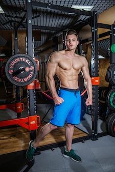 大きな筋肉とジムでの幅広いバックトレイン、フィットネス、そして腹部の圧迫感を備えたスポーティな男性。ダンベルとジムでセクシーな男。