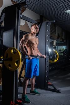 大きな筋肉を持つスポーティな男で、ジム、フィットネス、腹部の圧迫された腹部プレスで背中を伸ばします。