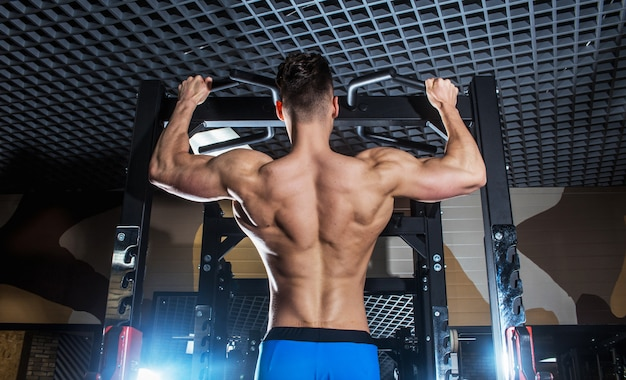 Sporty man with big muscles and a broad back trains in the gym, fitness and pumped-up abdominal press