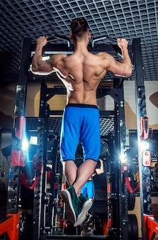 Sporty man with big muscles and a broad back trains in the gym, fitness and pumped-up abdominal press.