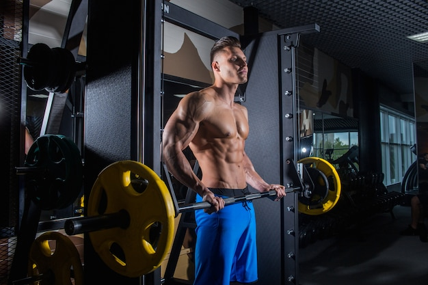 Sporty man with big muscles and a broad back trains in the gym