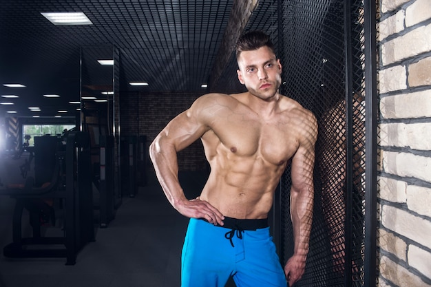 Sporty man with big muscles in the gym, fitness and pumped-up abdominal press