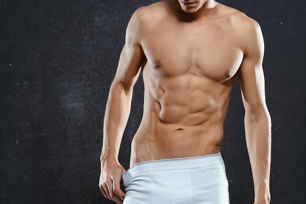 トレーニングで筋肉質の体の白いパンティーを持つスポーティな男