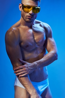 Sporty man with pumped body bodybuilder fashion glasses studio