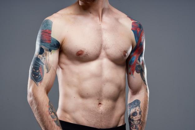 펌핑 된 복근을 가진 스포티 한 남자가 팔 근접 촬영에 문신을 자른 모습