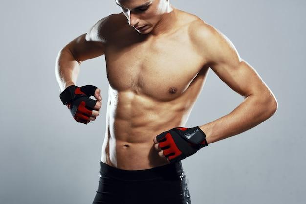 ボクシンググローブのトレーニングエクササイズで体をポンプでくみ上げたスポーティな男