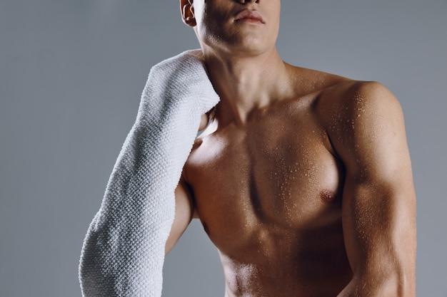 Спортивный мужчина с накачанными полотенцами для тела в руках крупным планом на изолированном фоне