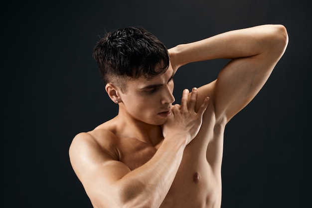 Sporty man with pumped up muscular body holds his hand behind his head posing