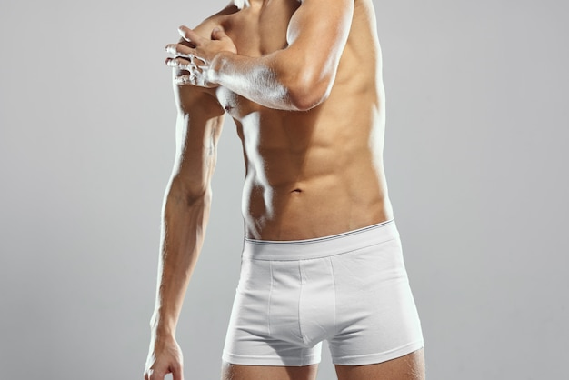 白いショートパンツワークアウト明るい背景で筋肉の体をポンプアップしたスポーティな男