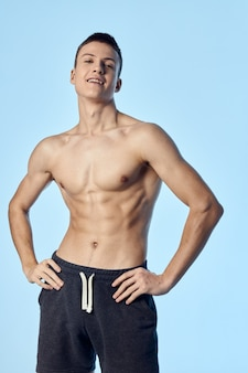 Sporty man with a pumped-up naked torso holds his hands on his belt posing blue background. high quality photo