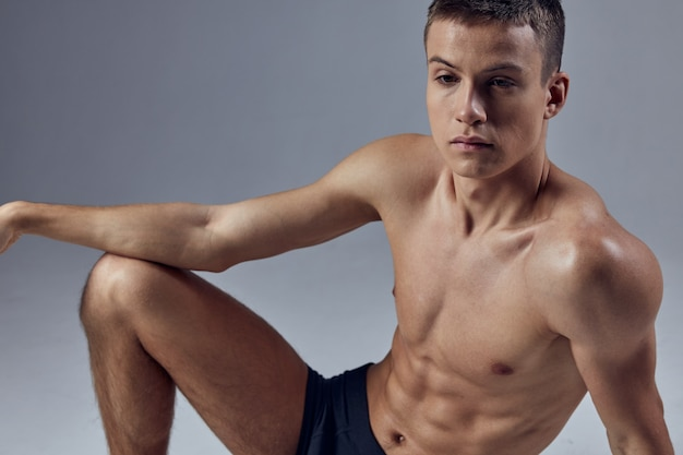 Sporty man with a pumpedup body in black shorts sits on the floor closeup