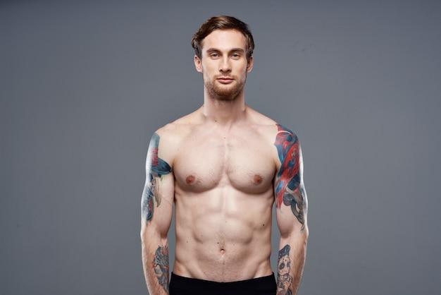 彼の腕のトレーニングクロップドビューに入れ墨を持つスポーティな男