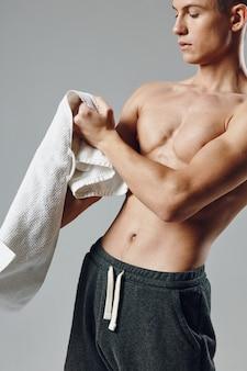 黒のショートパンツワークアウトスタジオで手にタオルを持つスポーティな男