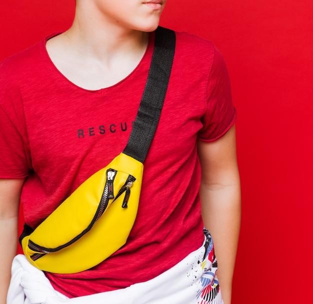 黄色いベルトバッグのストリートウェアスタジオ撮影でスポーティな男。縦の写真