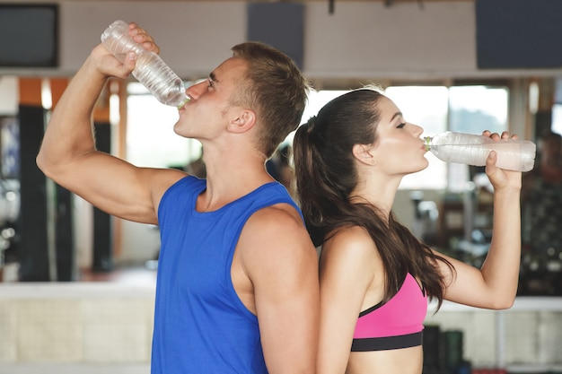 Sporty man and woman drinking mineral water back to back