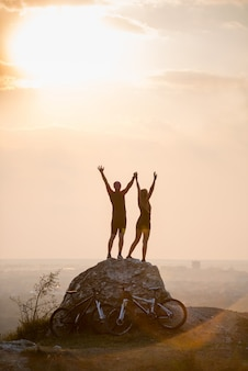 Sporty man and woman standing on large stone hands up