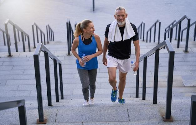 Спортивная зрелая пара мужчина и женщина в спортивной одежде выглядят довольными, поднимаясь по лестнице после