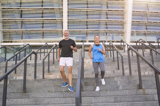 朝の街で一緒にトレーニングスポーツウェアのスポーティな成熟したカップルの男性と女性