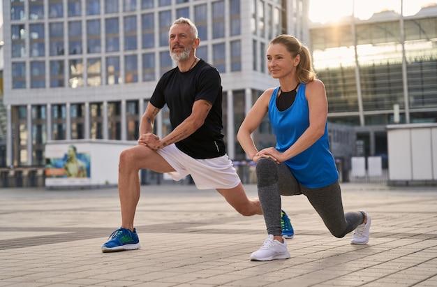 スポーティな成熟したカップルの男性と女性が街で一緒に走る準備をしてウォーミングアップ