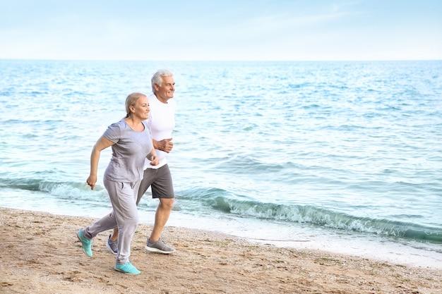 Спортивная зрелая пара работает на морском пляже