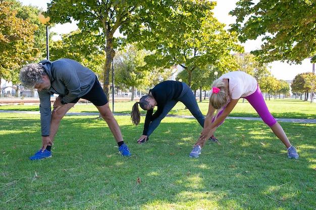 Persone mature sportive che fanno esercizio mattutino nel parco, in piedi sull'erba e corpi di pesca. pensionamento o concetto di stile di vita attivo