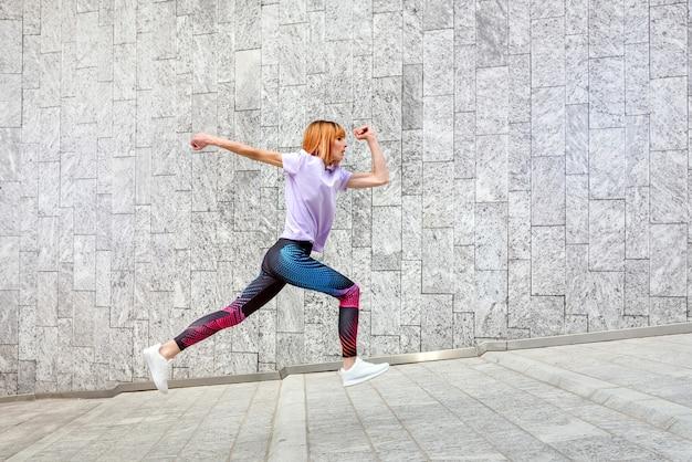 Спортивная зрелая женщина, бегущая трусцой по городу, пробегая по склону мимо коммерческих зданий, в здоровом активном образе жизни на открытом воздухе и концепции фитнеса