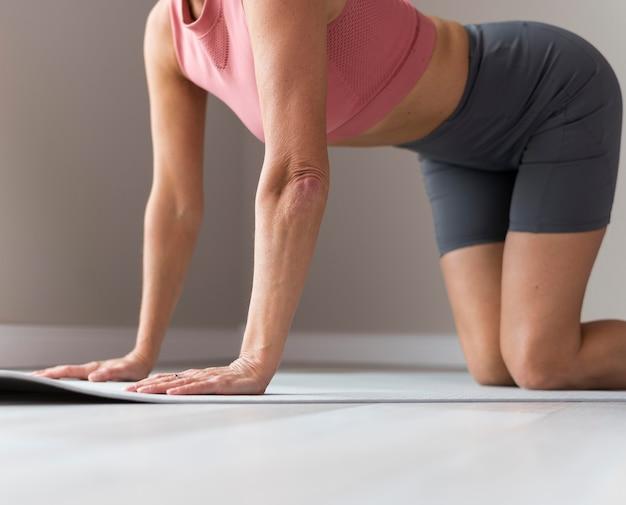 ピンクのタンクトップとワークアウトの練習をしているスポーティな成熟した女性