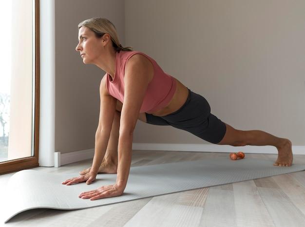Спортивная зрелая женщина с розовой майкой делает упражнения для тренировки