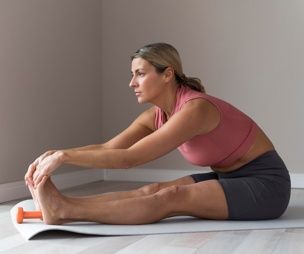 Sporty mature woman with pink tank top stretching