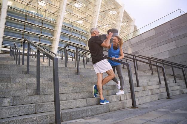 屋外で一緒に運動した後、お互いにハイタッチをするスポーティな中年夫婦