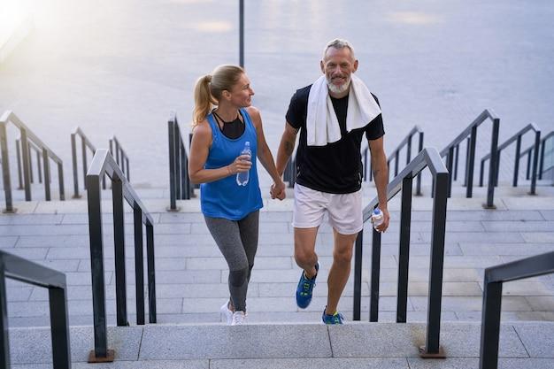 Спортивная влюбленная пара средних лет, мужчина и женщина в спортивной одежде, выглядят счастливыми, держась за руки, пока