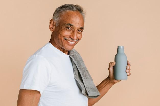 水のボトルを保持しているスポーティな混合インド人