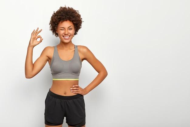 Спортивная модель в спортивной одежде показывает нормальный жест рукой, уверяет, что все в порядке, другую руку держит на талии