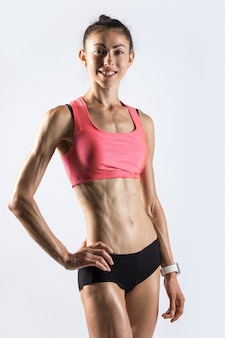 Sporty model with beautiful body posing in studio