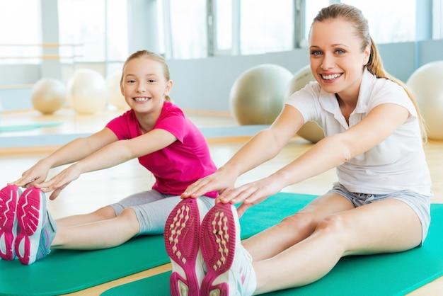 스포티한 엄마와 딸. 쾌활한 엄마와 딸이 스트레칭 운동을 하고 스포츠 클럽에서 운동 매트에 앉아 웃는 동안