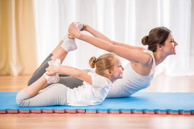 Sporty mother and daughter doing yoga exercises.