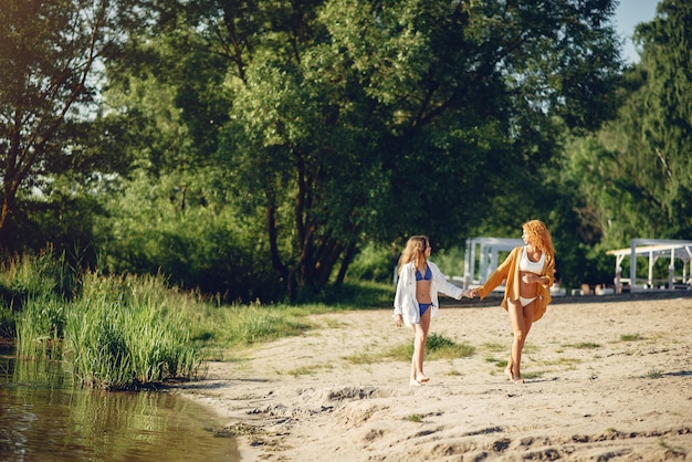 Sporty mother with cute daughter walking near lake