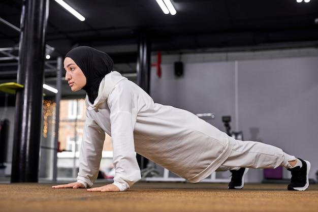 腕立て伏せをしているスポーティなイスラム教徒の女性、板の運動をしているフィットネスの女性。ヒジャーブのやる気のある女性はジムの床でトレーニングを楽しんでいます