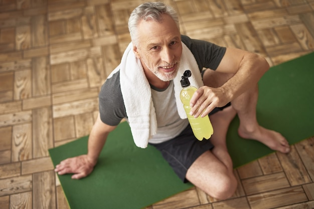 Sporty old man drinks water on mat physiotherapy.
