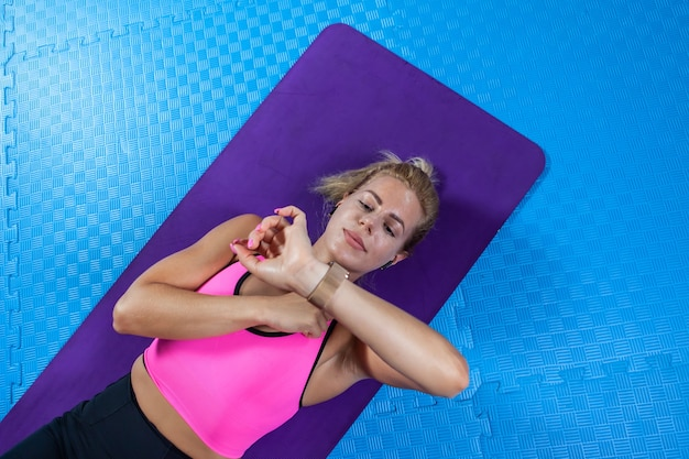 Sporty people, healthy lifestyle. young active woman with slim body relaxing after abdominal crunches exercise on yoga mat and looks at watch in fitness class.
