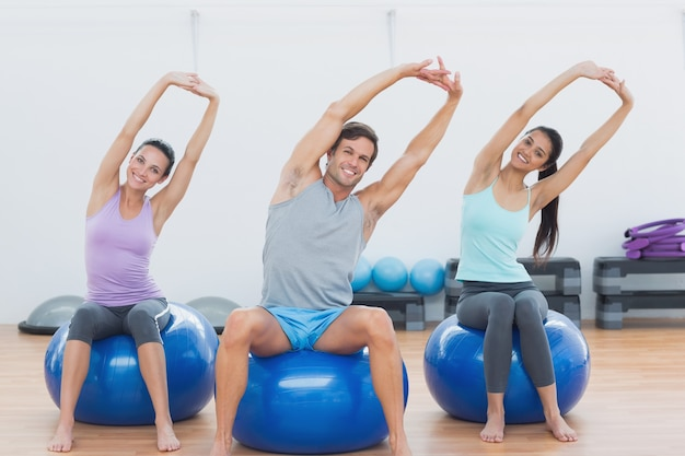 Sporty people stretching up hands on exercise balls at gym